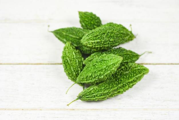 Zucca amara sfondo zucche amare verdi verdi fresche su legno bianco, altri nomi momordica charantia e melone amaro