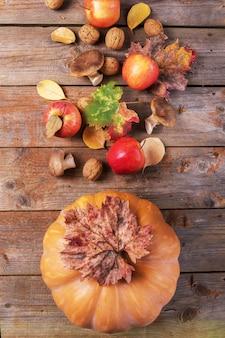 Zucca arancione con funghi cardoncelli, mele, noci e foglie colorate su vecchie tavole di legno rustici.