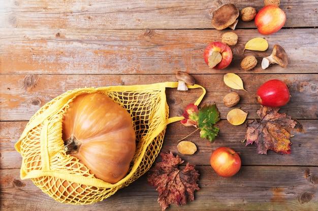 Zucca autunnale in un sacchetto di cotone ecologico a rete con mele, funghi cardoncelli, noci, foglie su assi di legno vecchi. shopping d'autunno, raccolta, zero rifiuti