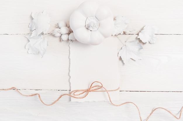 Zucca bianca, bacche e foglie e foglio bianco di carta e corda di lino