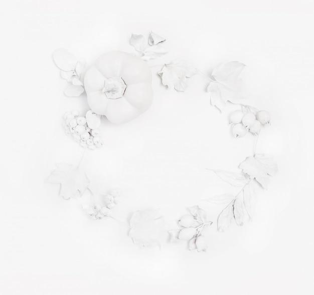 Zucca bianca, bacche e foglie su un pavimento di legno bianco