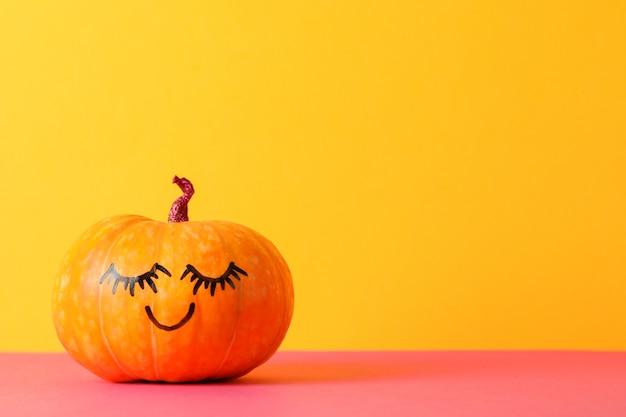 Zucca con il sorriso contro il giallo, spazio per il testo