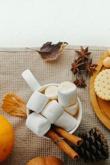Zucca con tazze di caffè. cacao caldo con marshmallow, biscotti, cannella. vista dall'alto