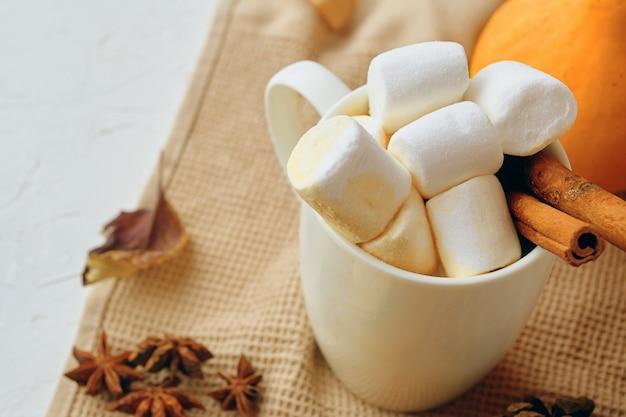Zucca con tazze di caffè. frullato di caffè al latte speziato con marshmallow e zucca. bevanda calda autunno inverno.