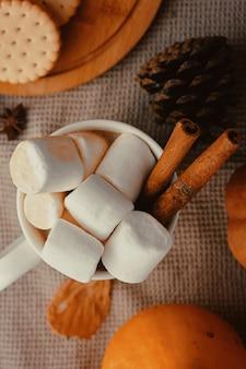 Zucca con tazze di caffè. tazza di caffè e zucca con marshmallow. sul tavolo di legno bianco