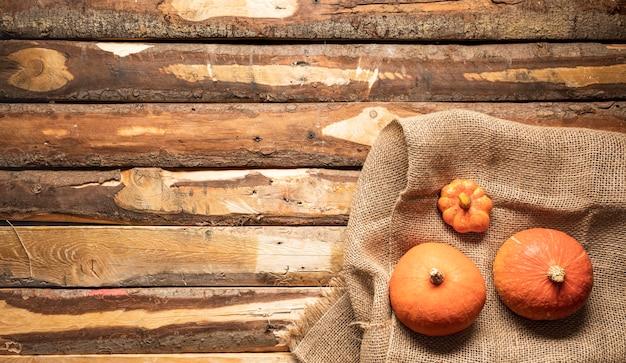 Zucca di disposizione piana sulla borsa della tela e fondo di legno