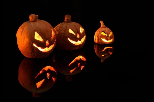 Zucca di halloween con candele accese su sfondo nero
