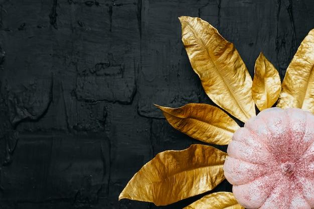 Zucca di halloween glitter rosa e foglie d'oro su sfondo nero