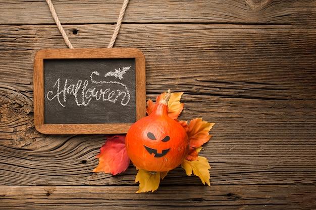 Zucca di halloween raccapricciante con foglie di autunno