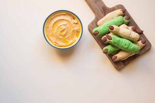 Zucca di hummus con il dito dei biscotti dell'insalata