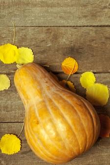 Zucca e foglie gialle sui bordi di legno
