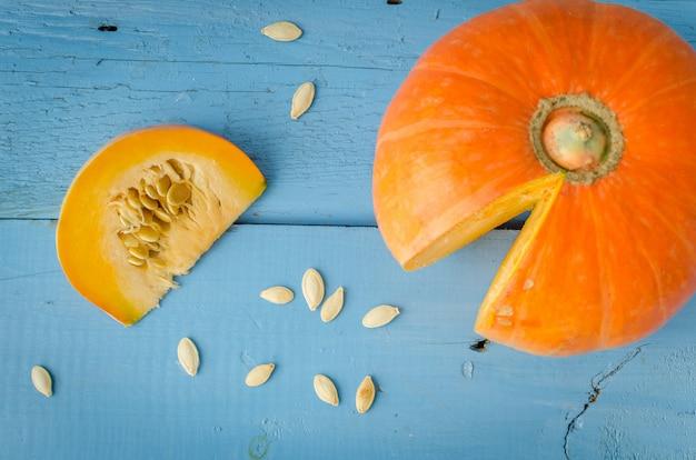 Zucca e semi di zucca su superficie di legno