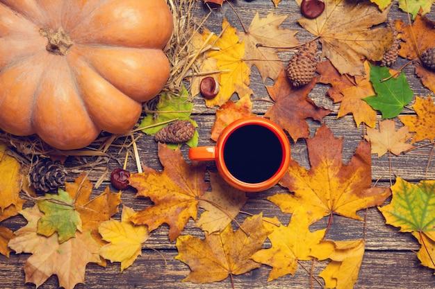 Zucca, foglie, castagne con cono e tazza di caffè su un tavolo di legno.