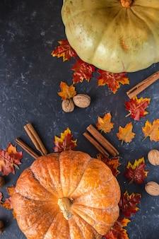 Zucca, ghiande, foglie gialle, cannella su uno sfondo scuro