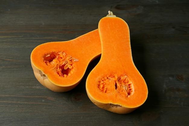 Zucca torta tagliata nel senso della lunghezza che mostra carne arancione viva sulla tavola di legno di marrone scuro