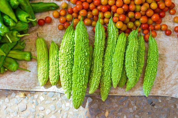 Zucche amare, pomodori e peperoncini verdi in vendita al mercato locale del mattino