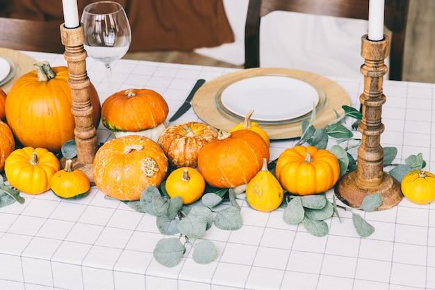 Zucche arancioni sulla tabella bianca in caffè