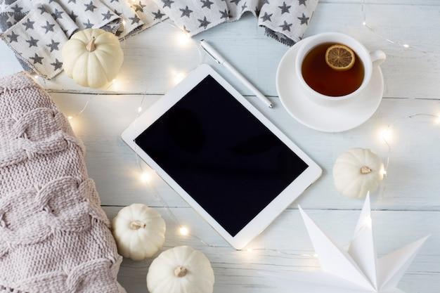 Zucche bianche, una tazza di tè con limone, una tavoletta, una penna, una ghirlanda e un plaid in maglia