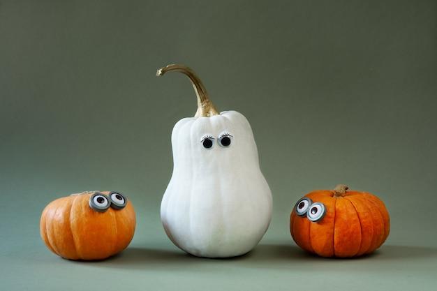 Zucche divertenti di halloween con gli occhi googly su verde