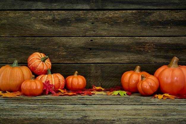 Zucche e foglie di autunno su di legno