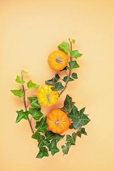 Zucche e foglie su sfondo pastello