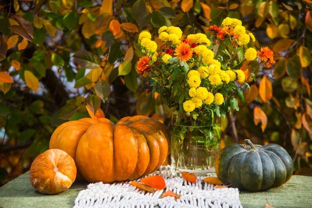 Zucche e un mazzo di fiori autunnali su un tavolo in giardino. stile rustico.