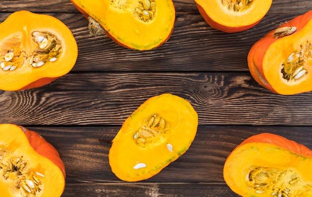 Zucche piane del taglio di disposizione su fondo di legno
