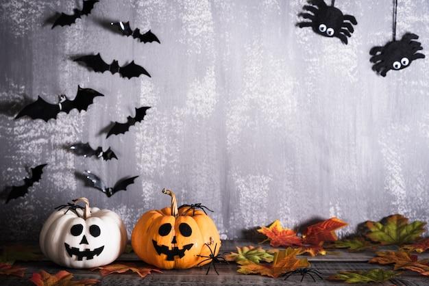 Zucche scolpite arancia di halloween con i pipistrelli e ragni su fondo di legno grigio