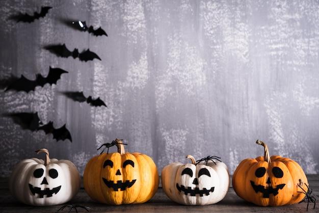 Zucche scolpite arancia di halloween su fondo di legno grigio con i pipistrelli.