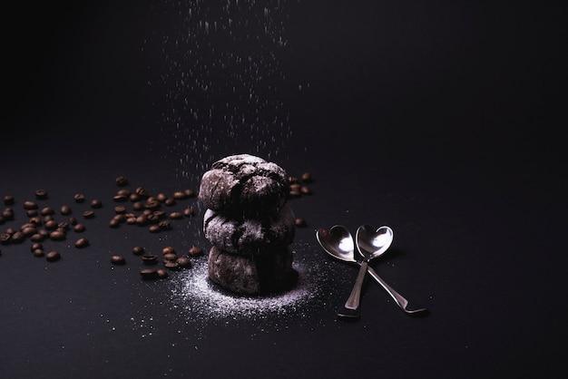 Zucchero a velo che cade su biscotti al cacao impilati con chicchi di caffè tostato e cucchiaio su sfondo nero