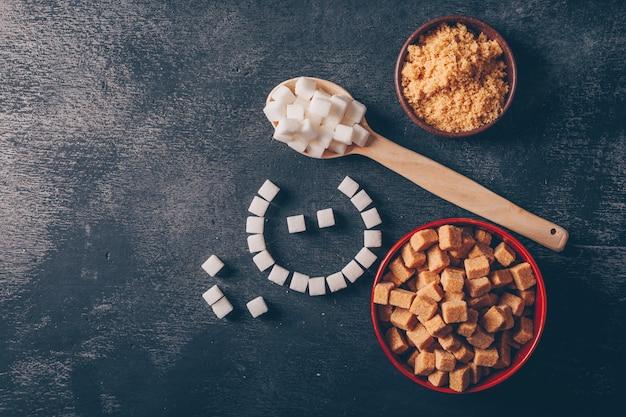 Zucchero bianco ed emoji in ciotole con cucchiaio piatto disteso