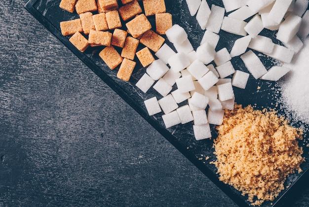 Zucchero bruno e bianco in un tagliere. vista dall'alto. copia
