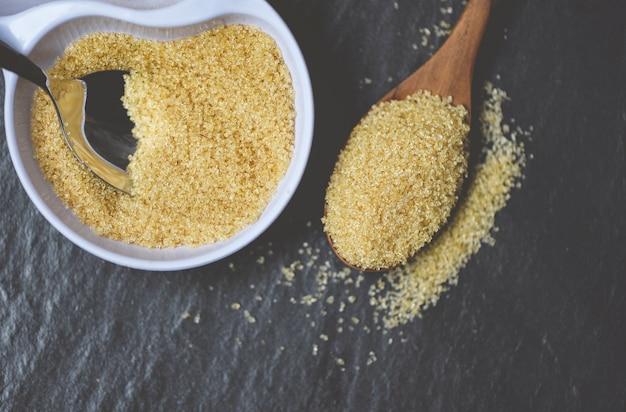 Zucchero bruno in cucchiaio di legno sul nero con lo zucchero di canna sulla ciotola bianca