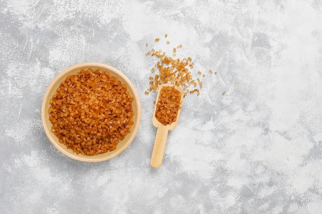 Zucchero bruno in piatto ceramico su calcestruzzo, vista dall'alto