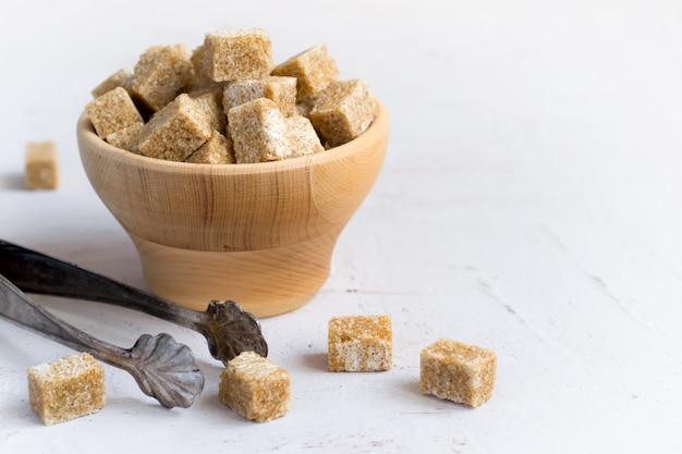 Zucchero bruno in una ciotola di legno, spazio della copia
