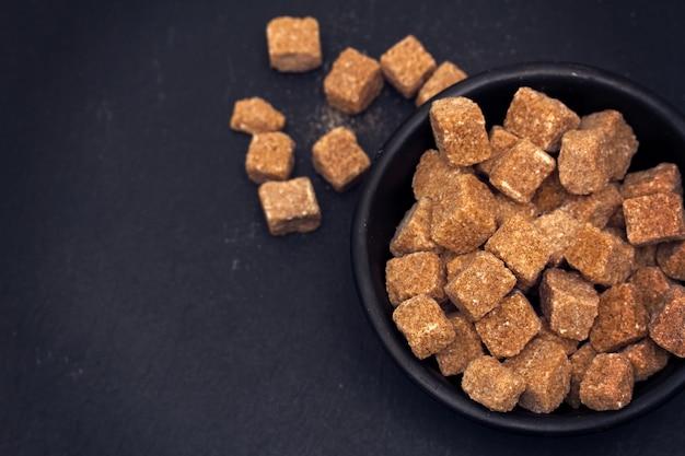 Zucchero bruno su superficie nera