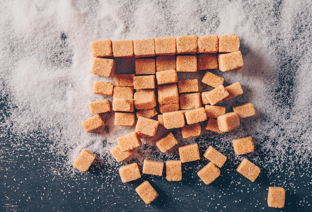 Zucchero bruno su una polvere di zucchero e su una tavola scura. disteso.