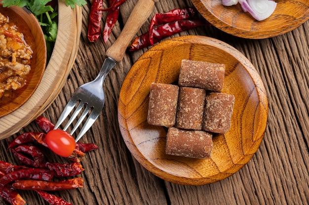 Zucchero di palma, cipolle rosse, peperoni secchi, pomodori, cetrioli, fagioli lunghi e lattuga in una ciotola.