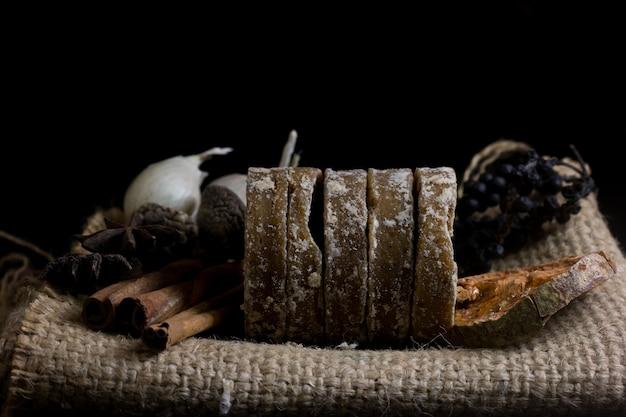 Zucchero di palma con aglio, bael secco, anice stellato isolato su sfondo nero