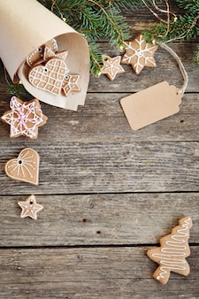 Zucchero di pan di zenzero casalingo tradizionale di natale che glassa in busta di carta su di legno.