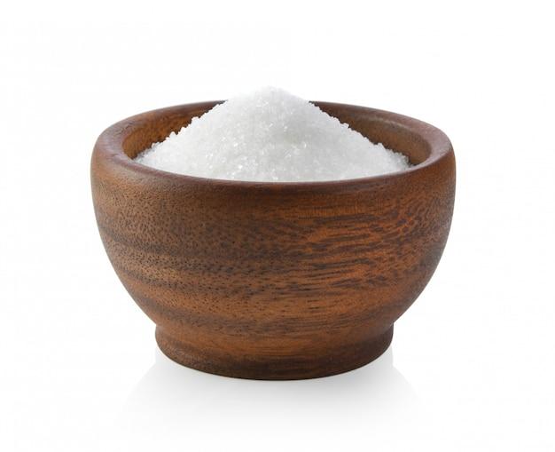 Zucchero dolce in ciotola di legno su superficie bianca