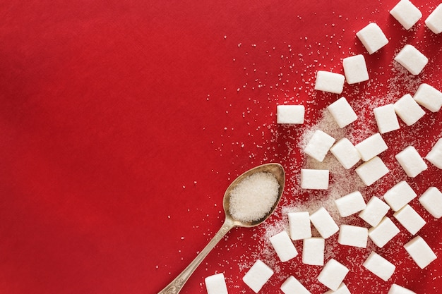 Zucchero e un cucchiaio su sfondo rosso