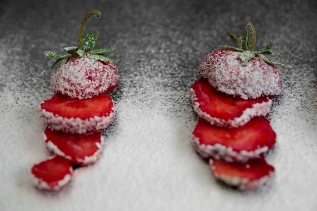 Zucchero in polvere belle fragole affettate sul nero. avvicinamento. estate
