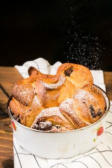 Zucchero in polvere spolverato sul dolce da forno in latta sul tovagliolo a scacchi sopra il tavolo