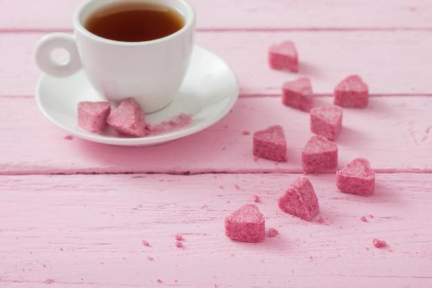 Zucchero rosa granulato a forma di cuore e tazza di tè su uno spazio di legno
