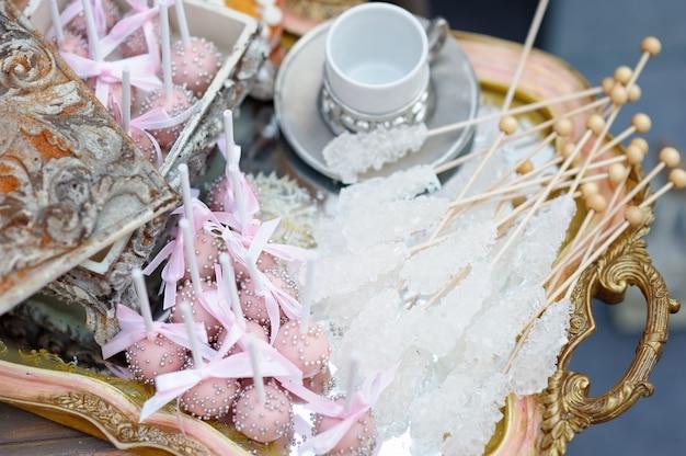 Zucchero su bastoncini e dolci rosa pop sul vassoio del tè