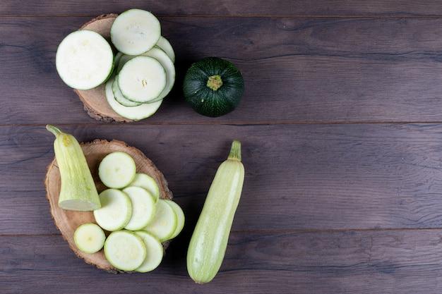 Zucchine a fette su tronconi e tavolo in legno scuro. vista dall'alto