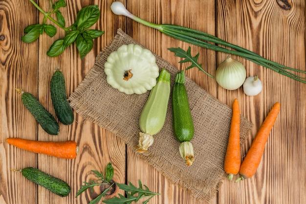 Zucchine, cetrioli, carote e verdure della verdura fresca su un fondo di legno