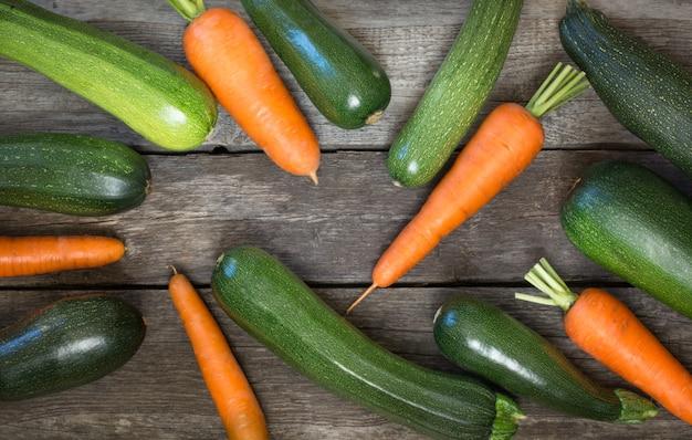 Zucchine e carote organiche fresche sulla tavola rustica. vista dall'alto