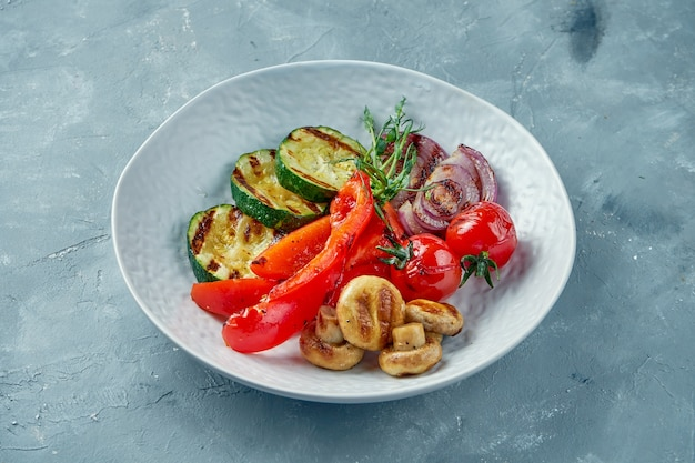 Zucchine grigliate, peperoni, cipolle, pomodori e funghi in una ciotola bianca. verdure grigliate piatto vegetariano